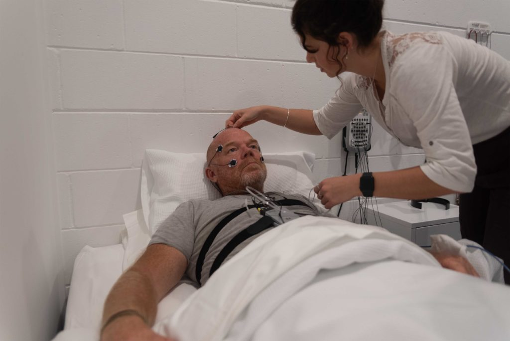 Man laying in bed at a sleep clinic doing Laboratory Sleep Studies
