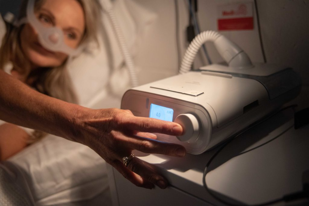Women in bed with a CPAP machine at a sleep clinic