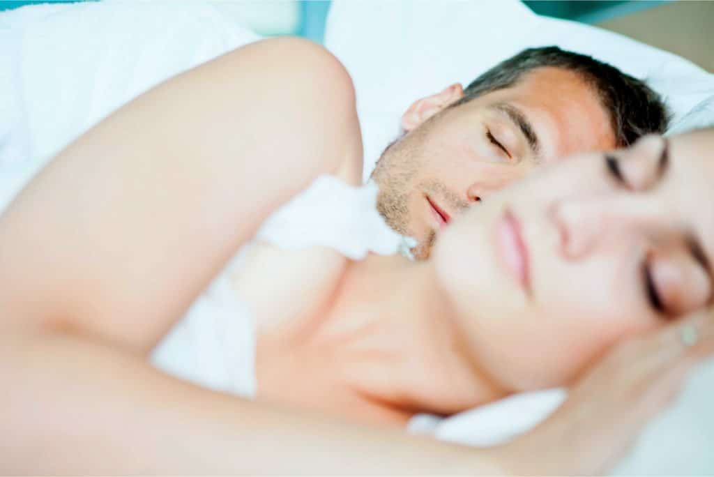 Sleep Studies at Home - Man and women laying in bed side by side and sleeping