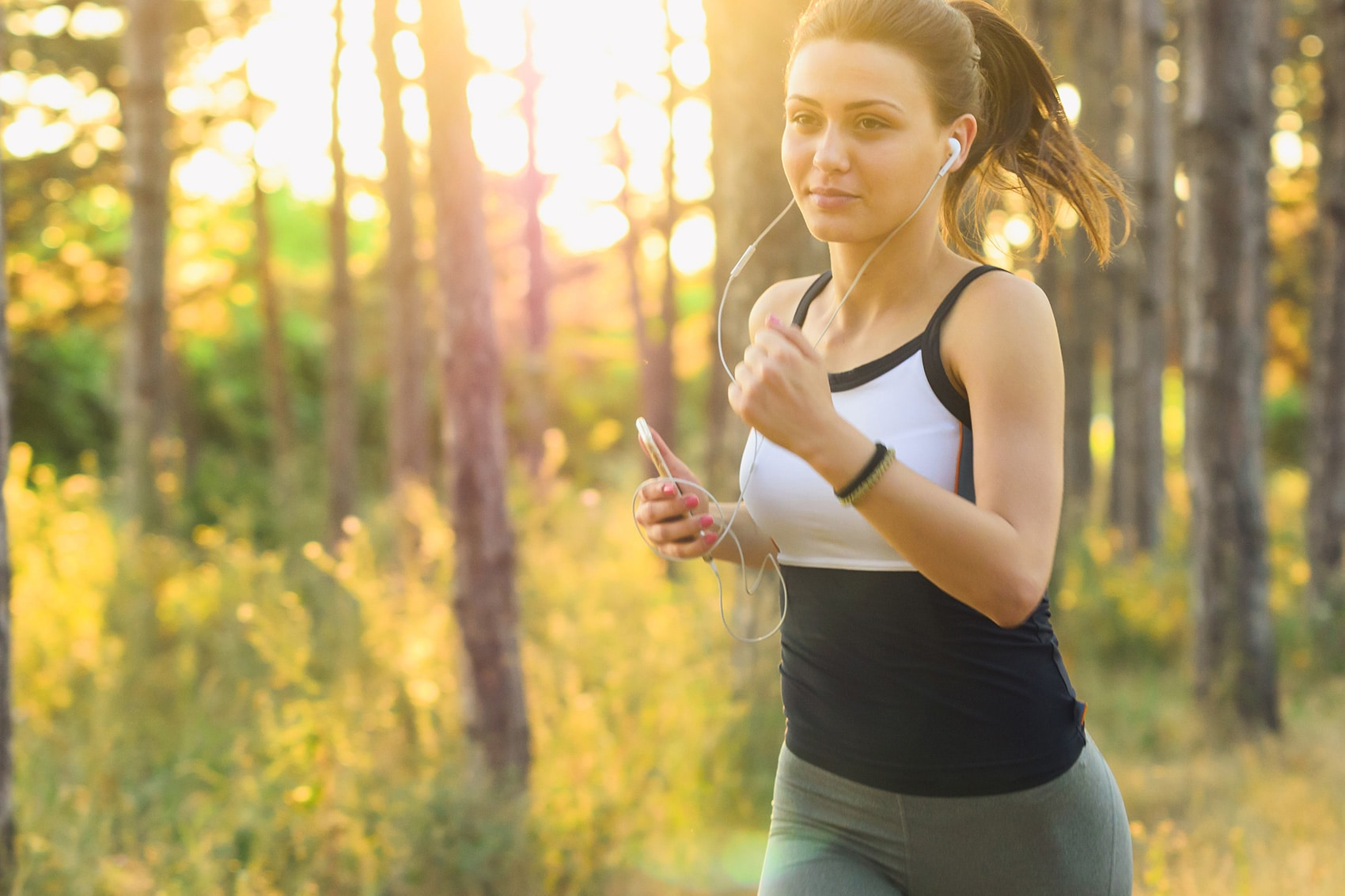 Young woman running in the nature holding a phone in her hand to listen music